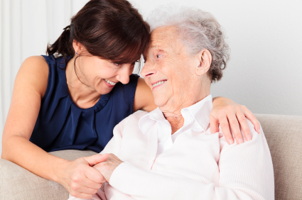 elderly woman and caregiver smiling at each other
